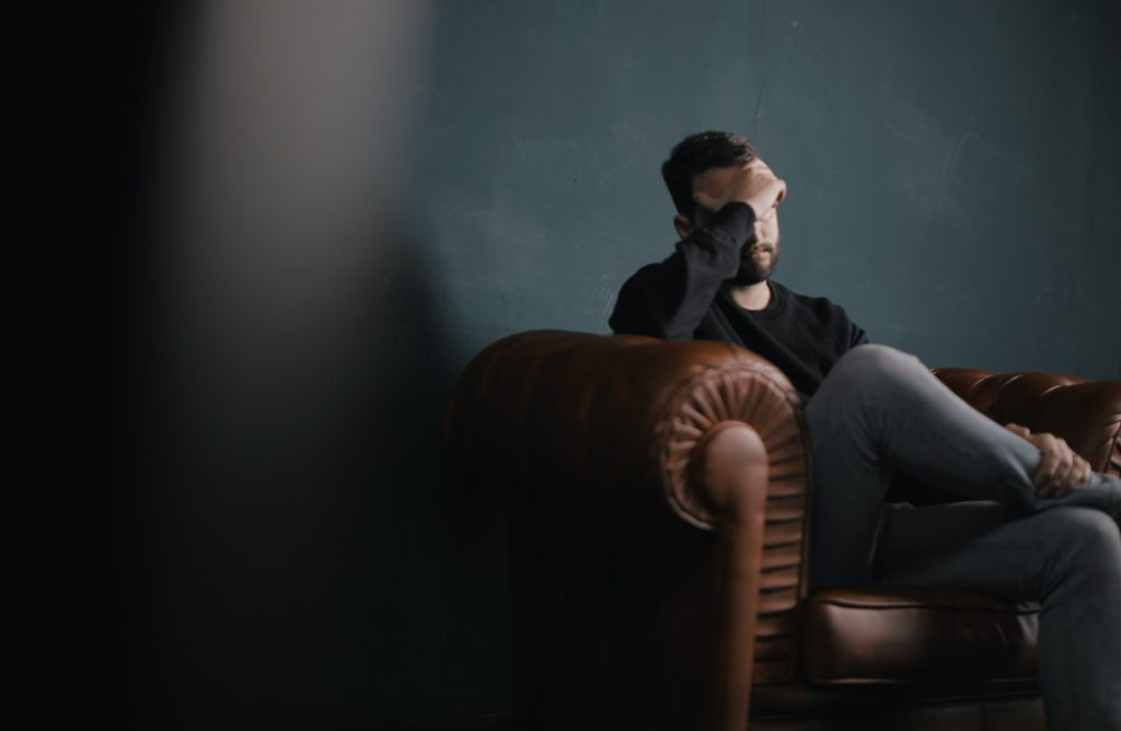 Sad man on leather couch